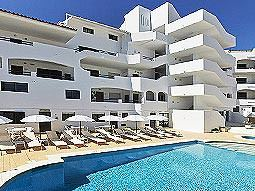 White building with an outdoor pool and sun loungers in the foreground