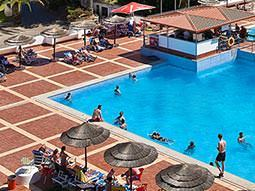 People in and around a large, outdoor swimming pool