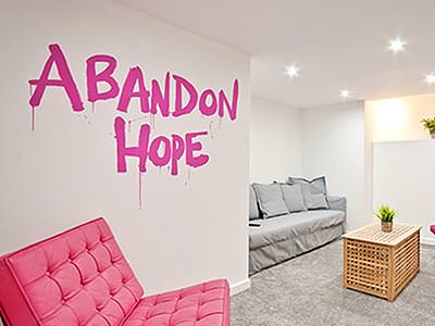 An apartment with pink and grey sofas and a coffee table, with the words abandon hope painted on the white wall