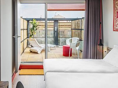 Two beds in a room with the windows to the French balcony open