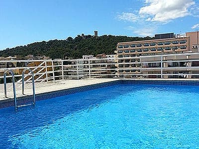 An outdoor pool with buildings and hills in the background