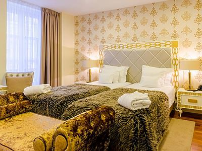 Two single beds in a double room, with patterned bedding, with a chaise longue at the foot of the bed