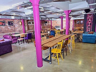 Tables and chairs and purple chesterfield sofas in the bar at Euro Hostel, Liverpool