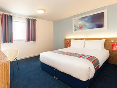 A double bed in a room with a blue carpet, and a runner matching the curtains lying over the bed