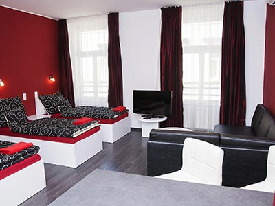 A red, white and black themed living room with recliner beds