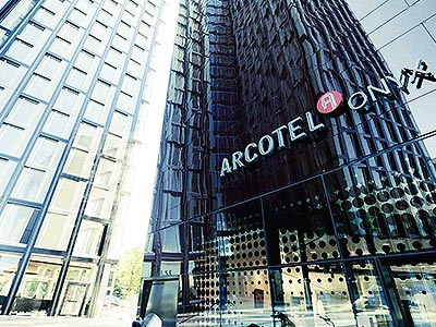 Glass exterior and sign of Arcotel Onyx during the day
