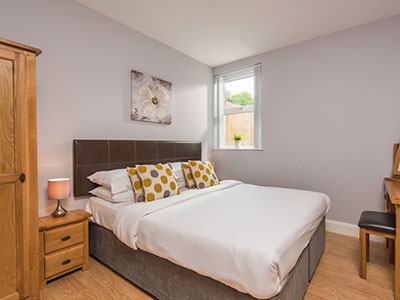 A double bed in a room with pine furniture and lilac walls