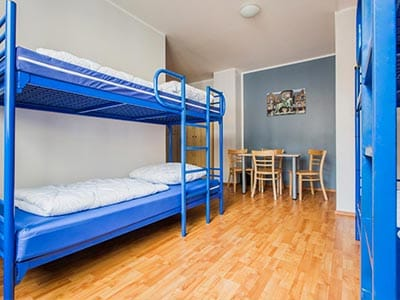 A bunk bed in a clean and tidy room with a wooden floor