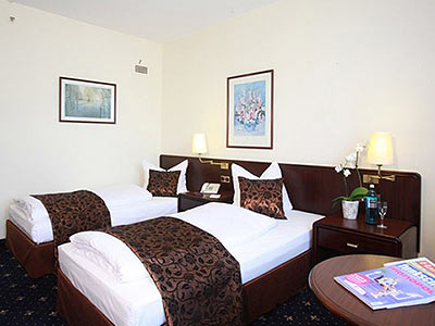 A neutral room containing two single beds, a bedside table and a round table with a magazine on it