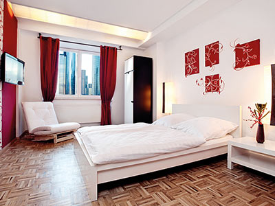 A white painted room with red accessories and a white bed