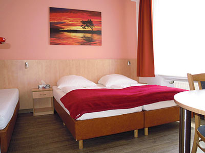 Two single beds on a wooden floor, with a painting hanging on the wall above