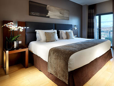 A double bed with brown and white bedding and a table with flowers on