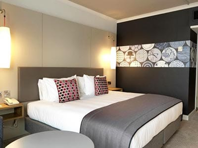 Image of a double bed with grey bed runner and a grey head board and a black wall with grey circle print and two lights attached to the wall each side of the bed
