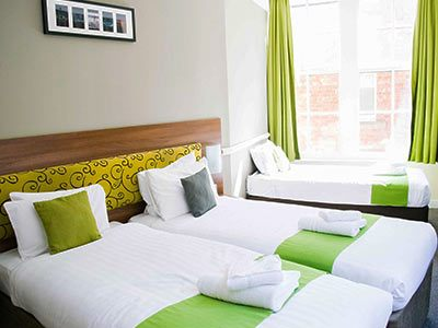 Three single beds in a room, with green pillows and throws on them