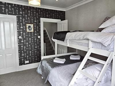 Image of a white wood bunk bed with a single and double bed with silver bedding