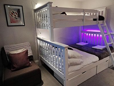 Image of a bunk bed with a double bed on bottom and single bed on top with purple neon lighting at the side of bunk