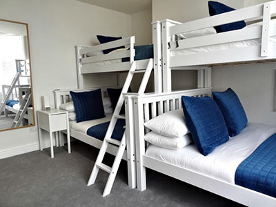 Various bunk beds in a white walled room