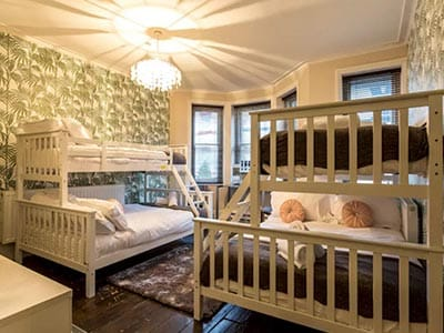 Image of a room with two white wood bunk beds with a green leaf feature wall and a chandelier