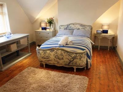 Image of a rooom with a tree designed fabric double bed with wood flooring and a big beige rug and grey furniture