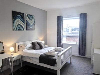 Image of a rooom with a white wood double bed and a window with grey curtains with white furniture