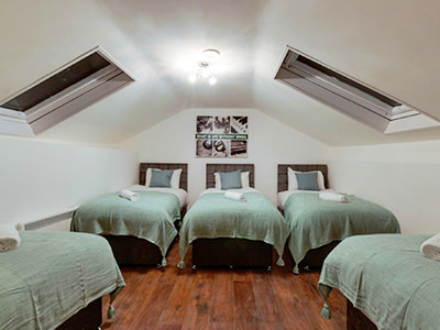 Five single beds in an apartment room with two large rooftop windows and wood flooring