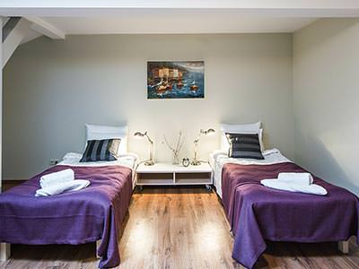 Two single beds with purple bedding in a spacious room