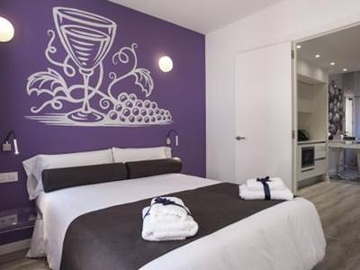 Image of a room with a double bed with white bedding and a grey bed runner with matching grey decoration cushions with a purple wall with a glass of wine and grapes painted on the wall