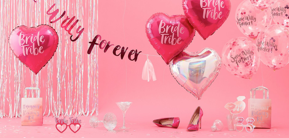 A collection of hen items including pink balloons, heart shaped glasses and party gift bags