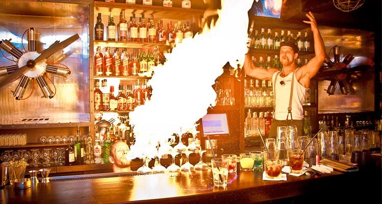 Image of a man blowing flames onto alcoholic drinks on the bar and a man standing behind the bar with his arms in the air