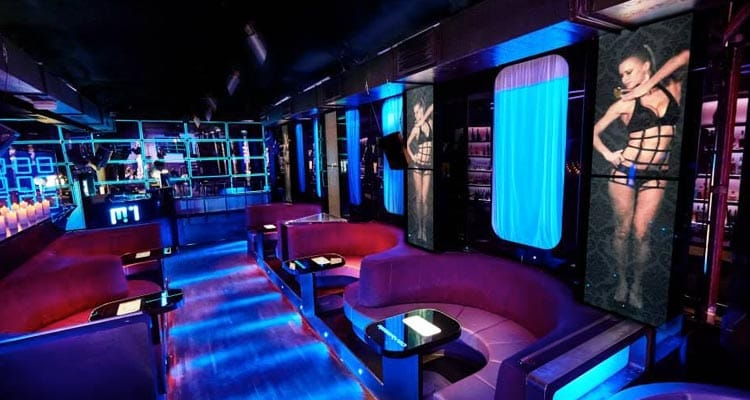A dark room with round corner red leather seats with tables in the middle and blue neon lights with images of women in their underwear on the wall
