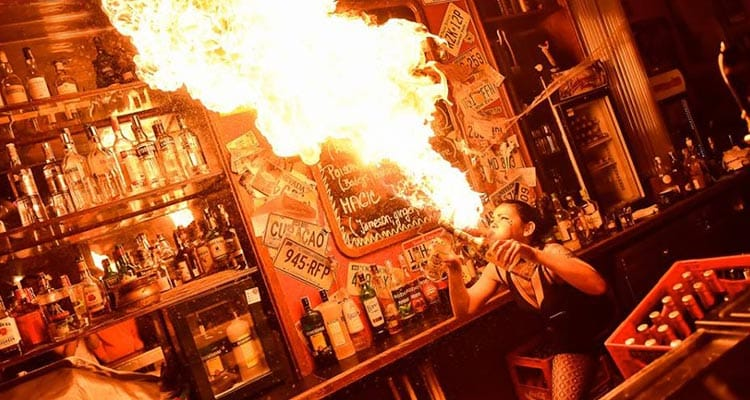 Image of a women blowing a huge flame behind a bar with alcohol