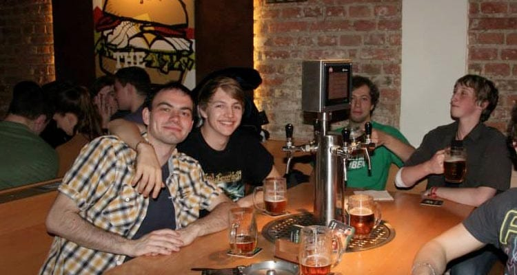 Image of a group of men sitting around a wooden table having pints poured from their very own pump