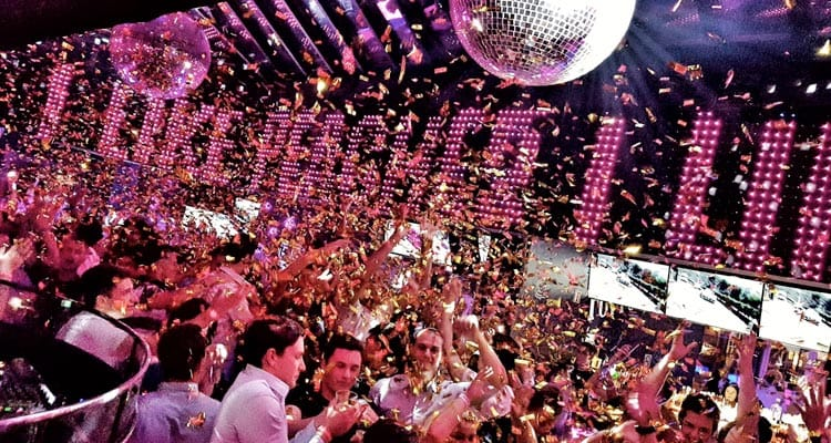 Image of people dancing in a bar with big disco balls and confetti coming down from the ceiling