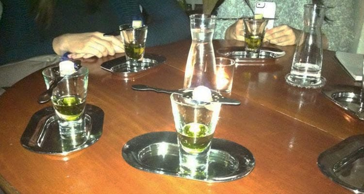 Close up image of a wooden table with shot glasses on small metal trays with a metal stirrer on top with a cube of sugar