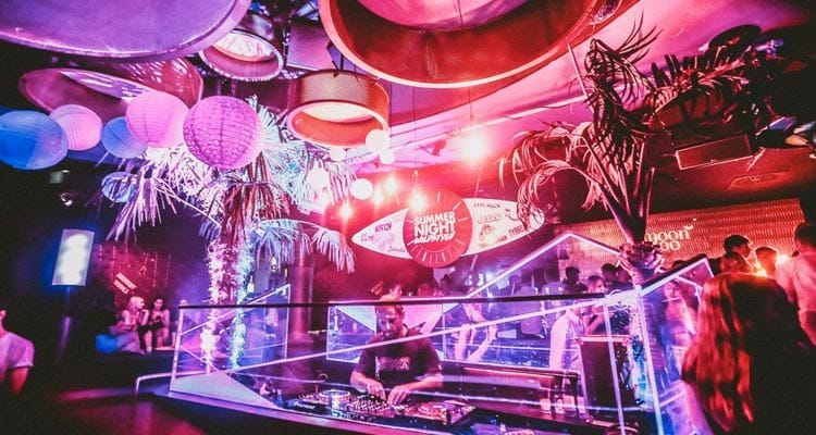 Image of a dj box and palm trees and different light fittings on the ceiling with orange and blue neon