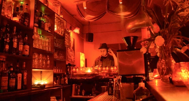 Image of a bar with the dj set up in the corner in a room with red lighting