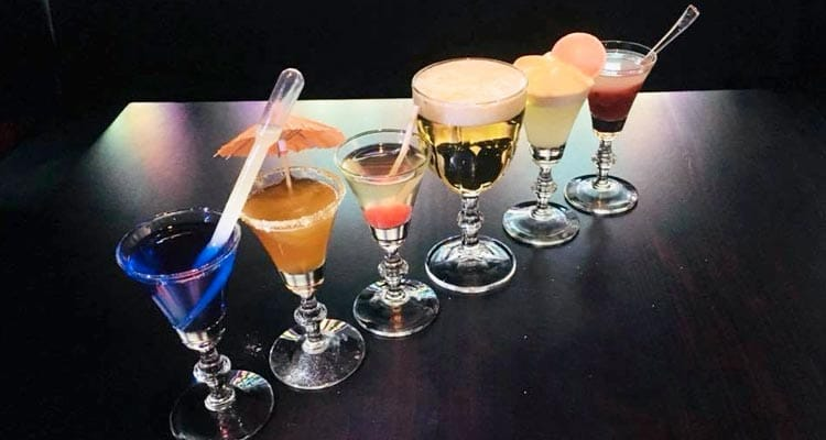 Image of a table lined with different coloured cocktrails with cocktail umbrellas and pipettes