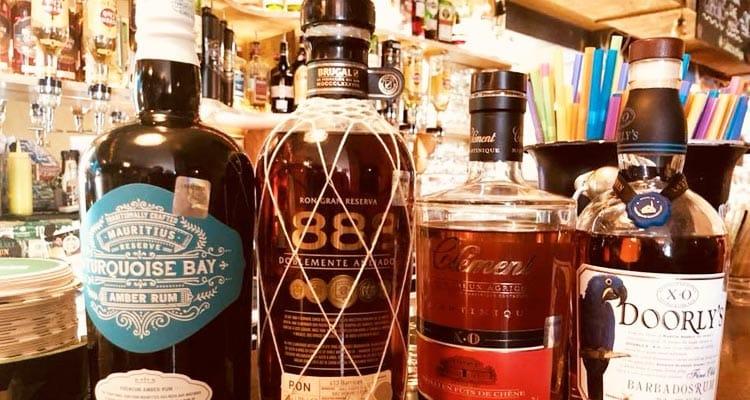 Close up image of dark spirit bottles on a bar