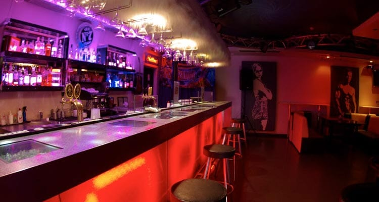 Image of the bar with round stools and pictures of women on the walls
