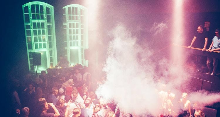 Image of a club filled with people on a dance floor next to the dj with smoke blowing onto the crowd