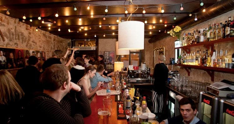 Image of people standing at the bar being served drinks