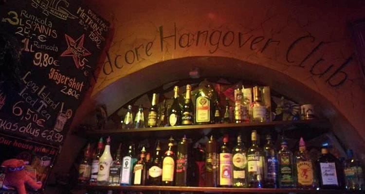 Image of two shelves holding spirits behind the bar with a chalk board with drink prices on