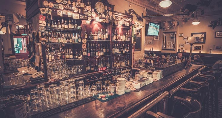Image of a bar with shelves of alcohol and glasses stacked up