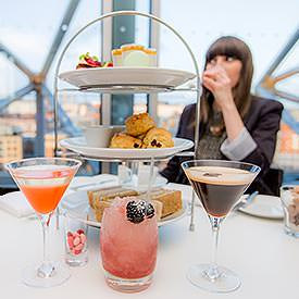 A girl enjoying an indulgent afternoon tea with cocktails in Newcastle's SIX Baltic restaurant