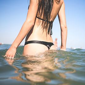 A close up of a woman wearing a black bikini, half submerged in the sea