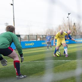 A goalkeeper in the foreground watching as two players tackle for the ball