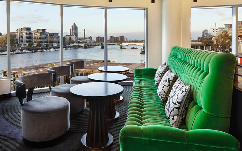 A green sofa facing tables and chairs, with the London skyline visible through the floor to ceiling windows