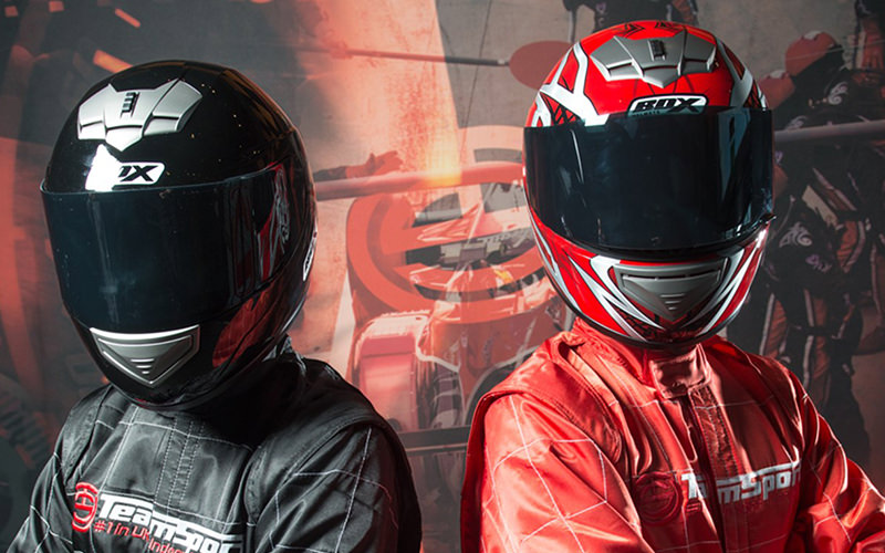 Two people wearing protective helmets and driving gear