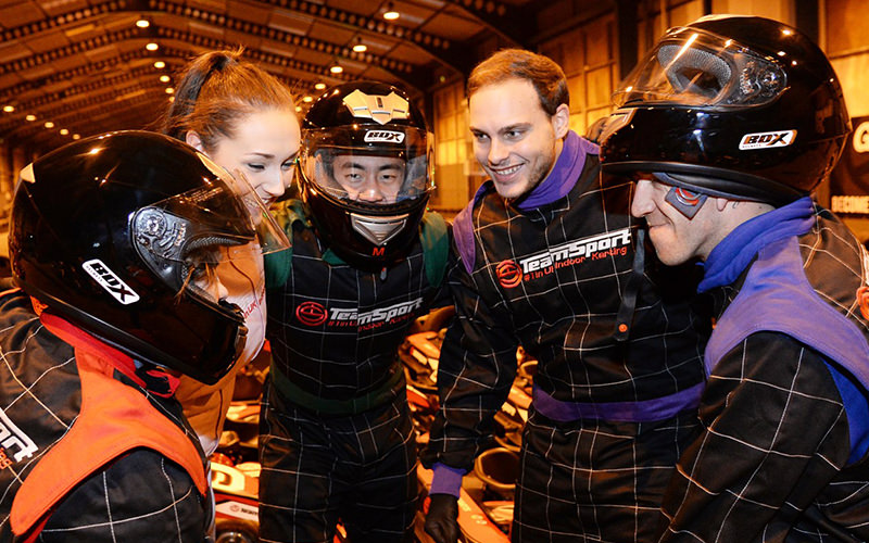 A group of people smiling together inside the karting arena