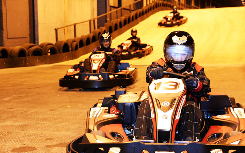 Four people driving around a track in karts